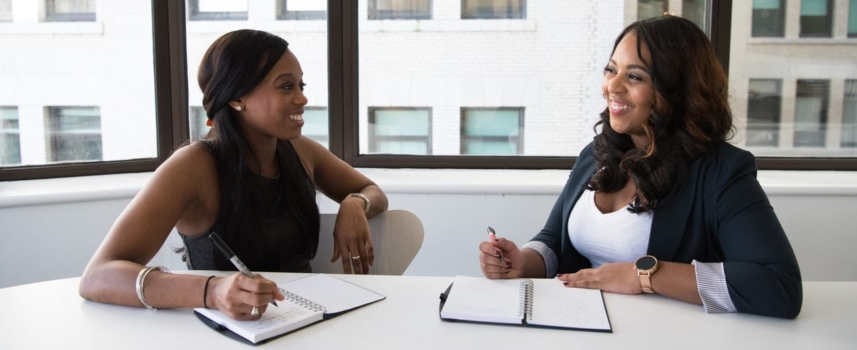 two women at a desk with notepads